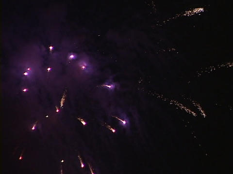 A display of fireworks explodes in the sky Stock Video Footage