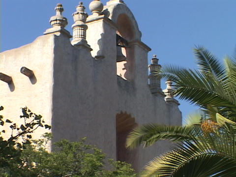 A bell hangs in an arch of an old Catholic mission Stock Video Footage
