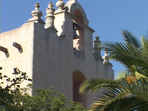 A bell hangs in an arch of an old Catholic mission Footage