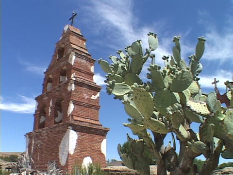 A cactus stands beside a bell tower at an old Catholic... Stock Video Footage