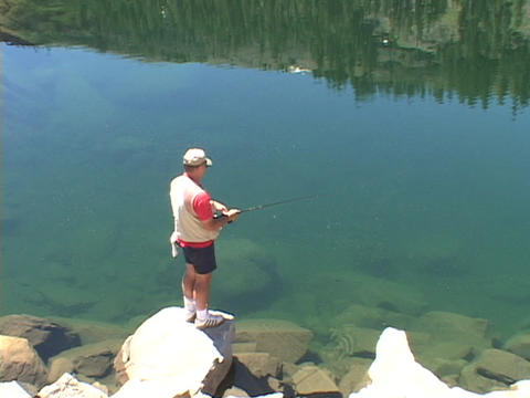 A fisherman fishes in high Sierra Lake Stock Video Footage
