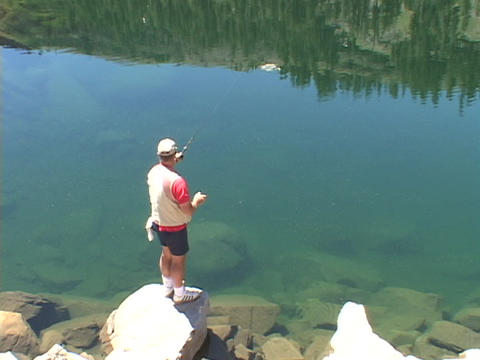A fisherman fishes in high Sierra Lake Footage