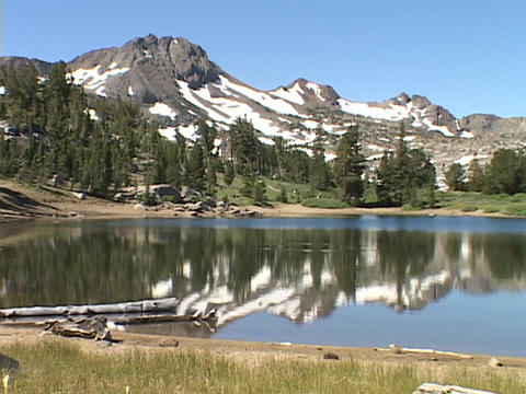 Mountains and trees reflect in a clear, calm lake Stock Video Footage
