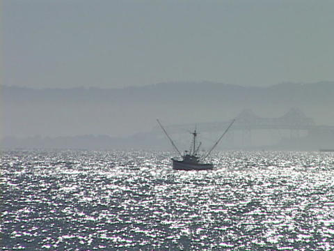 A commercial fishing boat travels on sparkling water Stock Video Footage
