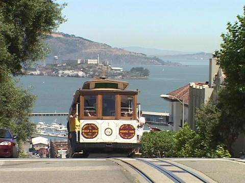 A cable car travels over a hill in San Francisco, California Footage