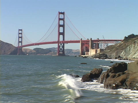 Waves crash on the shore near the Golden Gate Bridge Stock Video Footage