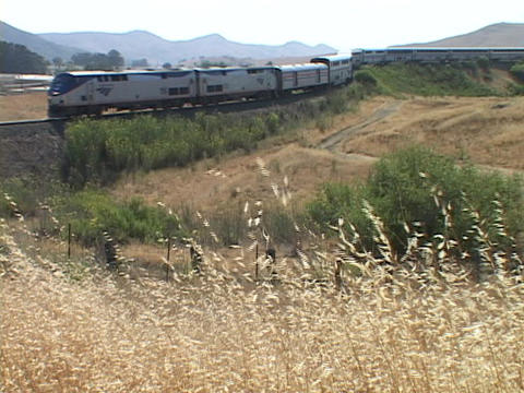An Amtrak passenger train rounds a bend and honks at a crossing Footage