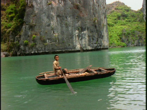 A Vietnamese boy rows a boat on green water in Halong... Stock Video Footage
