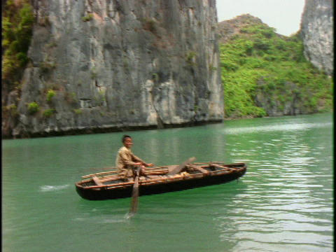 A Vietnamese boy rows a boat on green water in Halong Bay, Vietnam Footage