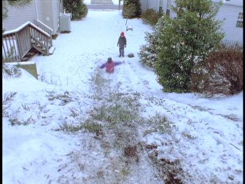 Children slide down a slick, snowy hill Stock Video Footage