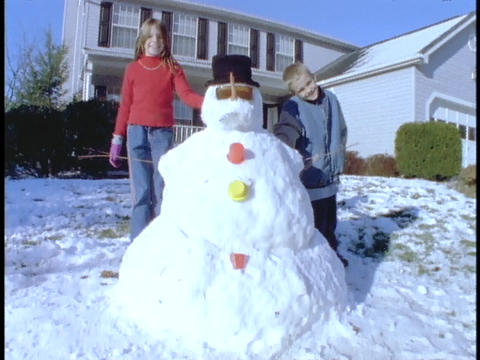Children stand next to a snowman in front of their house Footage