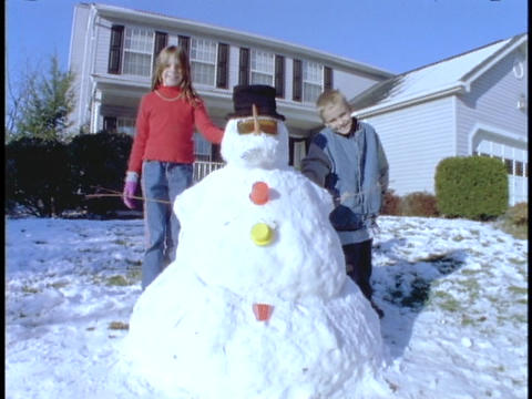 Children stand next to a snowman in front of their house Stock Video Footage