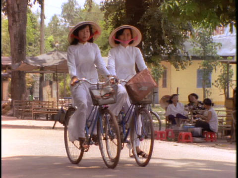 girls ride on bicycles in traditional Vietnamese dresses Stock Video Footage