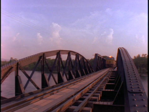 An Asian passenger train crosses a bridge Stock Video Footage