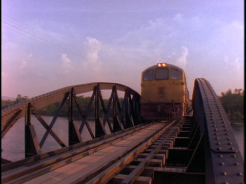 An Asian passenger train crosses a bridge Footage