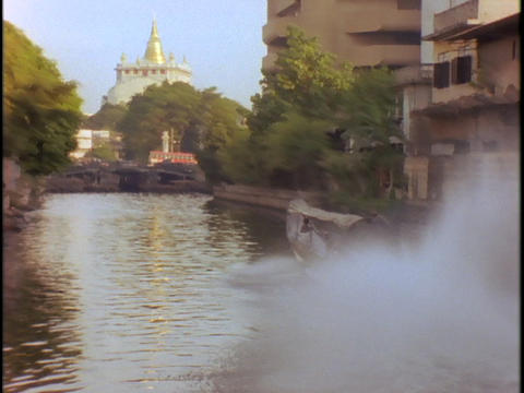 Buildings line a canal near a temple in Bangkok, Thailand Live Action
