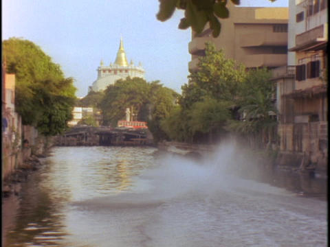 Buildings line a canal near a temple in Bangkok, Thailand Stock Video Footage