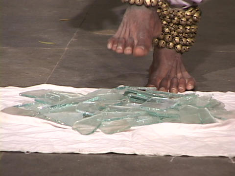 A bare-foot mystic steps on broken glass Live Action