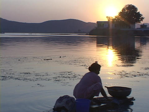 A woman washes clothes at golden-hour next to a lake Stock Video Footage