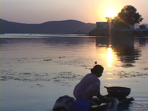 A woman washes clothes at golden-hour next to a lake Footage