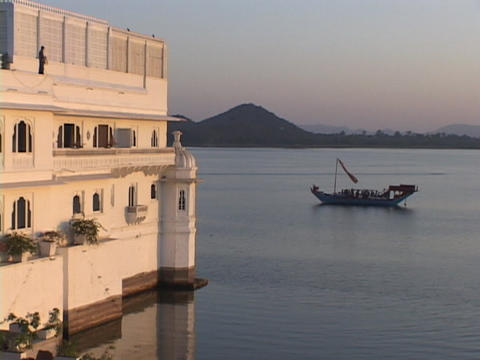 A boat floats on a lake near a palace in Udaipur, India Stock Video Footage