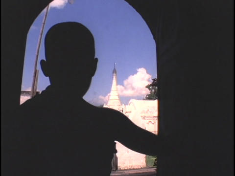 A young monk opens a door to reveal Buddhist pagodas and temples in Myanmar Footage
