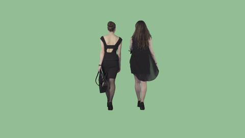 Two attractive young ladies in black formal dresses are walking from the camera Live Action