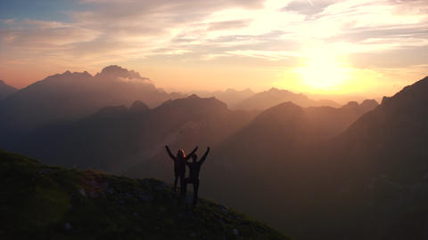 Aerial, edited - Flying backward over hiking couple with raised arms at sunset Footage