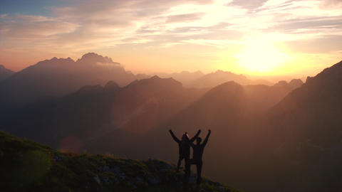 Aerial - Flying backward over hiking couple with raised arms in the mountains Footage