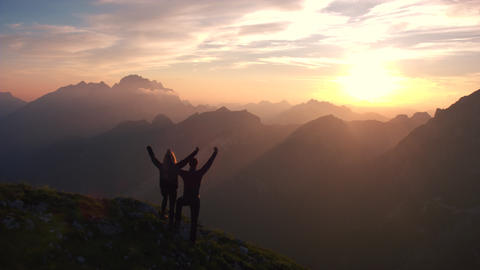 Aerial - Flyover silhouette of a couple with raised arms on the mountain Footage