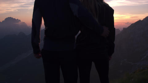 Jib shot - Embraced couple raises their arms in the mountains at sunset Footage