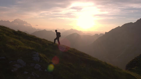 Aerial - Epic shot of a man hiking on the edge of the mountain as a silhouette i Footage