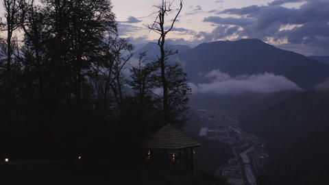 Tourist people relaxing in gazebo on hill with beautiful landscape on night city in mountains. Archivo