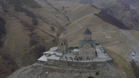 Aerial around view ancient georgian church on highland on Kazbegi mountain. Old orthodox temple Live Action