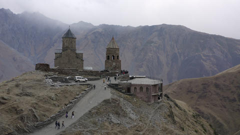 Aerial view ancient georgian church on highland on Kazbek mountain. Old orthodox temple Gergeti ビデオ