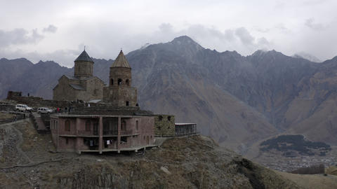 Ancient church Gergeti on Kazbek mountain background drone view. Aerial landscape old orthodox Footage