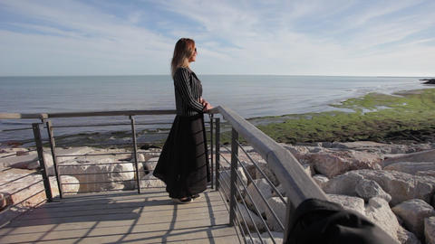 Woman with black elegant dress moved by the wind watching the sea on the horizon Footage