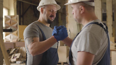 Two Caucasian builders shaking hands and smiling. Two men working at the Live Action