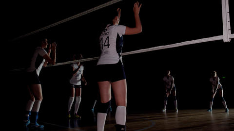 Women in uniform are playing volleyball, professional team, dramatic lighting Live Action