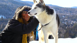Girl petting a husky outside in winter Live Action
