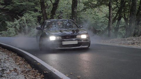 Black car starting with skidding and smoke on countryside road. Japanese jdm car driving with slip ビデオ