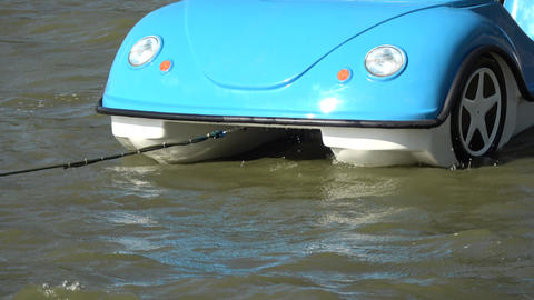 Plastic blue azure boat in shape of cars on sea water waves Live Action