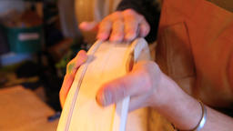 Hands of an artisan making sacred drum Live Action