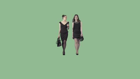 Two beautiful young women in black formal dresses are walking at the camera Live Action