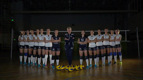 Female volleyball team is posing, squad photoshoot, coach and players Live Action