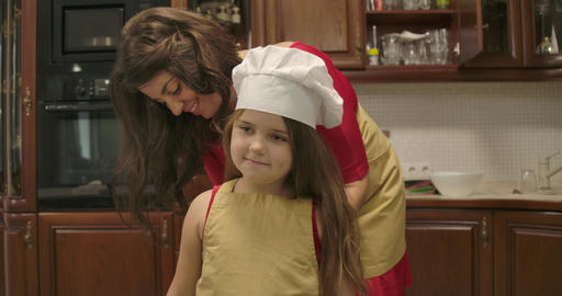 Pretty Caucasian girl in cook hat staying at kitchen as her mother putting apron Footage