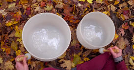 Young man plays crystal bowls in autumn ビデオ