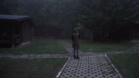 Lonely, lost girl walking between abandoned log cabins with her cellphone ライブ動画