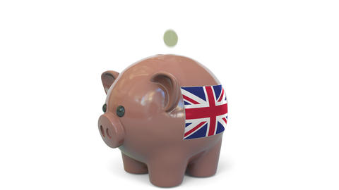 Putting money into piggy bank with flag of the United Kingdom. Tax system system Live Action