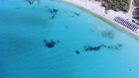 Aerial footage of beautiful beach with white sand and loungers on turquoise crystal clear sea Footage